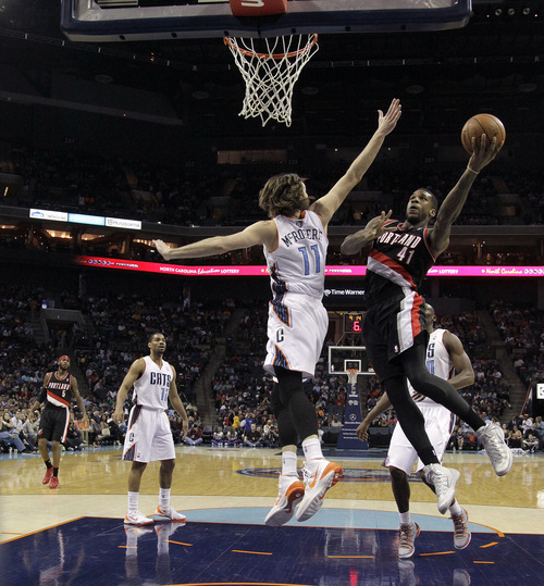 Portland Trail Blazers' Thomas Robinson (41) gets his shot off around Charlotte Bobcats' Josh McRoberts (11) during the first half of an NBA basketball game in Charlotte, N.C., Saturday, March 22, 2014. (AP Photo/Bob Leverone)