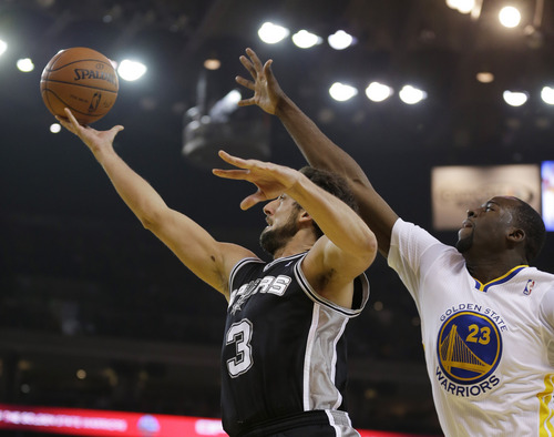 San Antonio Spurs guard Marco Belinelli, left, goes to the basket as Golden State Warriors forward Draymond Green, right, defends during the second quarter of an NBA basketball game Saturday, March 22, 2014, in Oakland, Calif. (AP Photo/Eric Risberg)