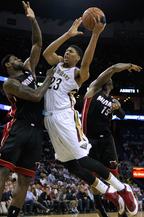 New Orleans Pelicans forward Anthony Davis (23) drives against Miami Heat forward LeBron James, left, and guard Mario Chalmers, right, during the second half of an NBA basketball game in New Orleans, Saturday, March 22, 2014. The Pelicans won 105-95. (AP Photo/Jonathan Bachman)