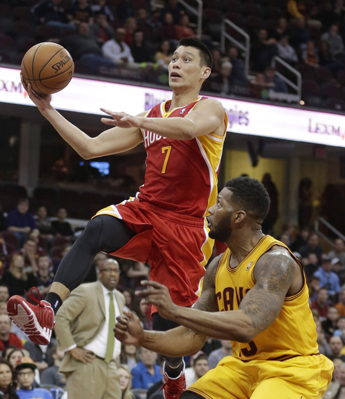 Houston Rockets' Jeremy Lin, left, jumps to the basket against Cleveland Cavaliers' Alonzo Gee during the fourth quarter of an NBA basketball game Saturday, March 22, 2014, in Cleveland. Houston defeated Cleveland 118-111. (AP Photo/Tony Dejak)