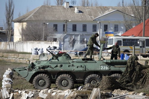 Pro-Russian soldiers in unmarked uniforms arrange a position on top an APC near Ukrainian marines base in the city of Feodosia, Crimea, Sunday, March 23, 2014. On Sunday, the Russian Defense Ministry said the Russian flag was now flying over 189 military facilities in Crimea. It didn't specify whether any Ukrainian military operations there remained under Ukrainian control. (AP Photo/ Pavel Golovkin)