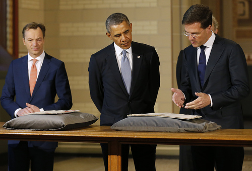 U.S. President Barack Obama, center, views the Act of Abjuration, widely considered to be the source document for the U.S. Declaration of Independence, during a tour of the Rijksmuseum with Museum Director Wim Pijbes, left, and Dutch Prime Minister Mark Rutte, right, during a visit at the Rijksmuseum in Amsterdam, Netherlands, Monday, March 24, 2014. Obama will attend the two-day Nuclear Security Summit in The Hague. (AP Photo/Frank Augstein)