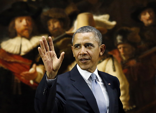 U.S. President Barack Obama waves in front of  Dutch master Rembrandt's The Night Watch painting during a visit to the Rijksmuseum in Amsterdam, Netherlands, Monday, March 24, 2014. Obama will attend the two-day Nuclear Security Summit in The Hague. (AP Photo/Frank Augstein)