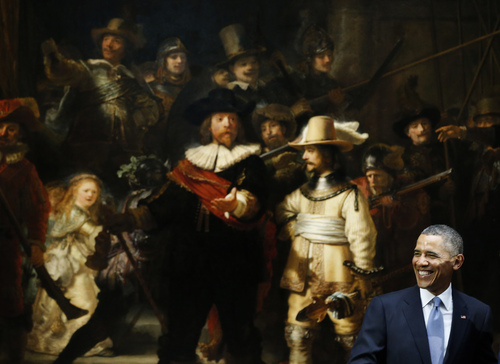 U.S. President Barack Obama smiles in front of  Dutch master Rembrandt's The Night Watch painting during a visit to the Rijksmuseum in Amsterdam, Netherlands, Monday, March 24, 2014. Obama will attend the two-day Nuclear Security Summit in The Hague. (AP Photo/Frank Augstein)