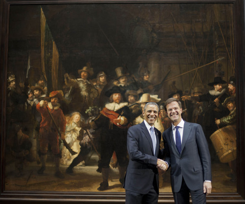 """U.S. President Barack Obama, left, and Prime Minister of the Netherlands Mark Rutte, right, shakes hands as they pose for photos in front of Rembrandt's """"The Nightwatch"""" painting at the Rijksmuseum in Amsterdam, Netherlands, Monday, March 24, 2014. Obama is attending the Nuclear Security Summit in The Hague, which will form the backdrop for an emergency meeting of Group of Seven leaders on Russia's annexation of Crimea. It's a confrontation between Russia and the West reminiscent of the Cold War. (AP Photo/Pablo Martinez Monsivais)"""