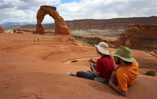 Francisco Kjolseth  |  The Salt Lake Tribune Mindy and Colby Tueller take in the beauty of one of Utah's most famous icons following their 1.5-mile trek to Delicate Arch in Arches National Park in late May.