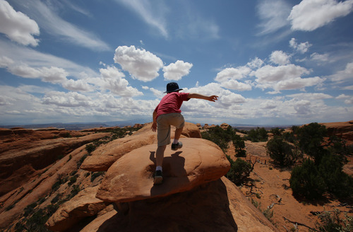Francisco Kjolseth  |  The Salt Lake Tribune Teo Droguett, 8, steps into the vast landscape that delights visitors from around the world every year at Arches National Park.