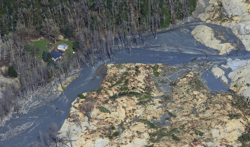 An intact house sits at left at the edge of the massive mudslide that killed at least eight people and left dozens missing is shown in this aerial photo, Monday, March 24, 2014, near Arlington, Wash. The search for survivors grew Monday, raising fears that the death toll could climb far beyond the eight confirmed fatalities. (AP Photo/Ted S. Warren)