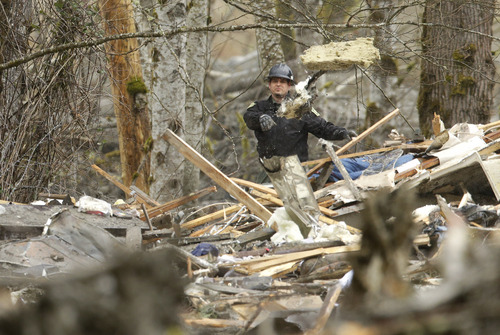 A U.S. Forest Service worker throws debris while working Tuesday, March 25, 2014, at a house that was destroyed on the western edge of the  massive mudslide that struck near Arlington, Wash., Saturday, killing at least 14 people and leaving dozens missing. (AP Photo/Ted S. Warren, Pool)