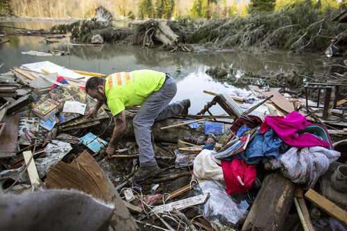 Iraq War veteran and local Little League coach Matt Pater, 32, searches through debris following Saturday's destructive mudslide, near Oso Wash, Monday, March 24, 2014. The search for survivors of Saturday's deadly mudslide grew Monday to include scores of people who were still unaccounted for as the death toll from the wall of trees, rocks and debris that swept through the rural community rose to at least 14. (AP Photo/seattlepi.com, Joshua Trujillo)