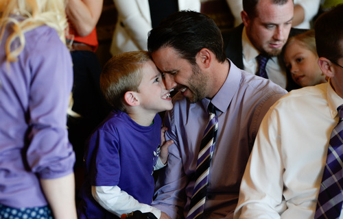 """Franciso Kjolseth     The Salt Lake Tribune Kyle Sintz of South Jordan shares a light moment with his son Isaac, 7, as they wait for Gov. Gary R. Herbert to sign a ceremonial version of HB105  to legalize the use of nonintoxicating cannabis oil by Utahns with untreatable epilepsy. Families gathered in the Gold Room at the Utah Capitol on Tuesday, March 25, 2014, for the signing. HB105, now called 'Charlee's Law,"""" will go into effect on July 1."""