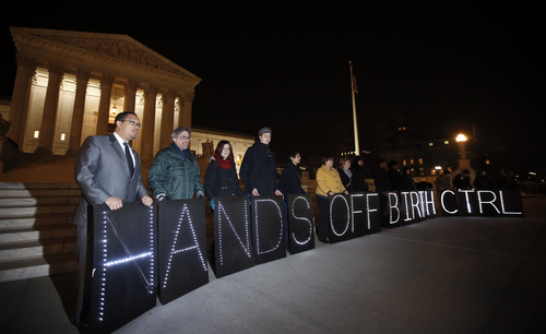 """A group of people organized by the NYC Light Brigade and the women's rights group UltraViolet, use letters in lights to spell out their opinion, in front of the Supreme Court, Monday, March 24, 2014 in Washington. Holding the """"H"""" in """"Hands"""" at left, is Rep. Keith Ellison, D-Minn. The Supreme Court is weighing whether corporations have religious rights that exempt them from part of the new health care law that requires coverage of birth control for employees at no extra charge. (AP Photo/Alex Brandon)"""