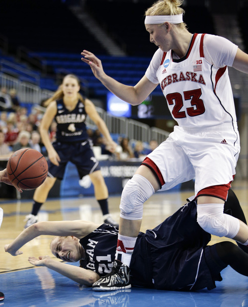 BYU's Lexi Eaton (21) falls to the court as Nebraska's Emily Cady (23) watches during the first half of a second-round game in the NCAA women's college basketball tournament on Monday, March 24, 2014, in Los Angeles. (AP Photo/Jae C. Hong)