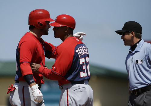 Washington Nationals' Bryce Harper, left, is held by first base coach Tony Tarasco as he argues with umpire Jeff Gosney, right, after Gosney ejected Harper in the fourth inning of an exhibition spring training baseball game against the St. Louis Cardinals, Wednesday, March 26, 2014, in Jupiter, Fla. (AP Photo/David Goldman)