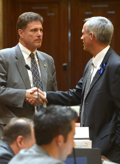 Leah Hogsten  |  The Salt Lake Tribune Rep. Jim Dunnigan, R-Taylorsville, chairman of the investigative committee is congratulated by Rep. Kay Christofferson, (right) after Dunnigan presented the final report, Wednesday, March, 12, 2014, to the Utah House, into former Attorney General John Swallow.  A stack of more than 200 pages with 3,700 exhibits was submitted as the result of a four-month, $4 million investigation, which contributed to Swallowís resignation.