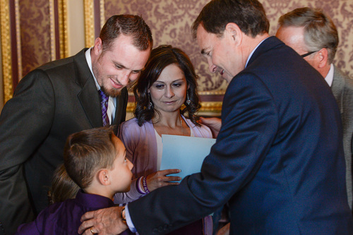 "Franciso Kjolseth  |  The Salt Lake Tribune Jeff and Catrina Nelson alongside their son Jericho, 10, meet with Gov. Gary R. Herbert to sign a ceremonial version of HB105  to legalize the use of nonintoxicating cannabis oil by Utahns with untreatable epilepsy. Their daughter, who could have benefited from the cannabis oil, recently passed away from Late Infant Batten Disease. Families gathered in the Gold Room at the Utah Capitol on Tuesday, March 25, 2014, for the signing. HB105, now called ""Charlee's Law,"" will go into effect on July 1."