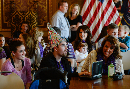 """Franciso Kjolseth     The Salt Lake Tribune Tyler Zimmerman, center, celebrates his 22nd birthday during a historical day following Gov. Gary R. Herbert to sign a ceremonial version of HB105  to legalize the use of nonintoxicating cannabis oil by Utahns with untreatable epilepsy. Families gathered in the Gold Room at the Utah Capitol on Tuesday, March 25, 2014, for the signing. HB105, now called """"Charlee's Law,"""" will go into effect on July 1."""