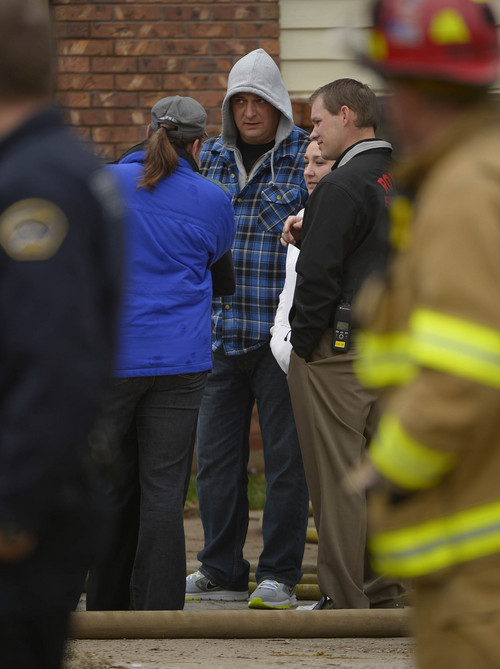 Leah Hogsten  |  The Salt Lake Tribune Residents discuss the fire as Roy firefighters cleanup the scene of an apartment fire that damaged six units and displaced 12-18 people, Wednesday, March 26, 2014 in Roy. Over 30 firefighters from Roy and five surrounding cities assisted in putting out the blaze that began shortly before 8am and spread quickly due to two propane tank explosions.