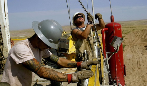 Chris Detrick  |  Tribune file photo  Roughnecks Mike Brandt, 27, of Vernal, right, and Jonathan Joe, 20, of Roosevelt, work on Pioneer Drilling Rig #54,about 30 miles south of Vernal in this July 2005 file photo. The workers work a 12 hour shift, 7 days in a row, then have 7 days off.