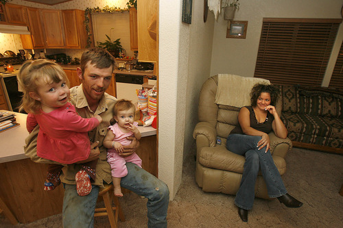 |  Tribune file photo  After a long day of work and a 90-minute drive back to his home in Vernal, Brandon Young  takes some time to be with his young daughters Maycee (2) and Shyann (11 months) as his wife Lavina  looks on with a smile in this 2006 file photo.