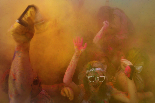 "Scott Sommerdorf   |  The Salt Lake Tribune People dance inside a cloud of yellow colors as the first ""throw"" of the 2013 Festival of Colors - Holi Celebration - takes place at the Krishna Temple in Spanish Fork, Saturday, March 30, 2013. The festival celebrates Holi, the announcement of the arrival of spring."