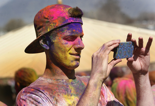 Scott Sommerdorf   |  The Salt Lake Tribune A celebrant full of colors makes a photo of friends at the 2013 Festival of Colors - Holi Celebration - takes place at the Krishna Temple in Spanish Fork, Saturday, March 30, 2013. The festival celebrates Holi, the announcement of the arrival of spring.