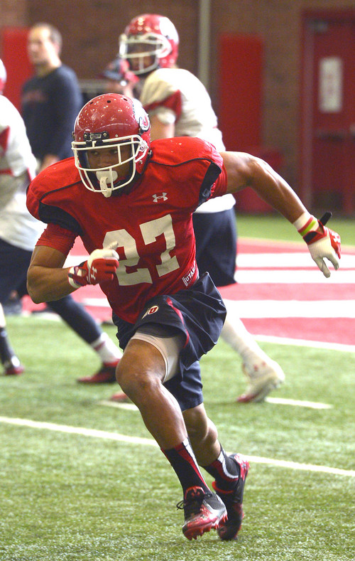 Leah Hogsten     The Salt Lake Tribune University of Utah running back Devontae Booker runs through plays with during practice Thursday, March 27, 2014 inside the Spence Eccles Field House.