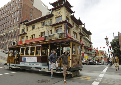 """Passengers disembark a cable car in the Chinatown district Thursday, March 27, 2014, in San Francisco. Beneath the strings of red paper lanterns and narrow alleyways of the nation's oldest Chinatown lies an underworld, a place with a history of opium dens, gambling houses and gangland murders. Federal investigators say it's also where Raymond """"Shrimp Boy"""" Chow operated a criminal empire while projecting a public image of community servant. The allegations against Chow are part of an FBI sting that names 25 other defendants, including state Sen. Leland Yee. (AP Photo/Ben Margot)"""