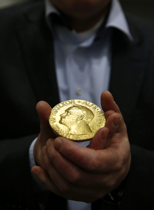 Bidder Ole Bjorn Fausa, of Norway, holds the 1936 Nobel Peace Prize medal in Baltimore, Thursday, March 27, 2014, the second Nobel Peace Prize ever to come to auction. It was won by an anonymous telephone bidder for $950,000. The recipient was Argentina's foreign minister, Carlos Saavedra Lamas, who was honored for his role in negotiating the end of the Chaco War between Paraguay and Bolivia. (AP Photo/Patrick Semansky)
