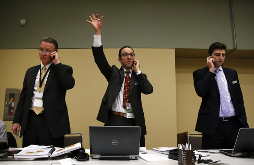 Vicken Yegparian, center, of Stack's and Bowers Galleries, signals a bid from a telephone bidder for the 1936 Nobel Peace Prize medal in Baltimore, Thursday, March 27, 2014. Pictured alongside Yegparian are John Konop, left, and Brian Kendrella, both of Stack's and Bowers. Only the second Nobel Peace Prize to come to auction, it was won by an anonymous telephone bidder for $950,000. The prize recipient was Argentina's foreign minister, Carlos Saavedra Lamas, who was honored for his role in negotiating the end of the Chaco War between Paraguay and Bolivia. (AP Photo/Patrick Semansky)