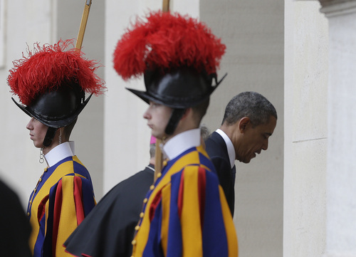 President Barack Obama walks past two Vatican Swiss guards as he arrives at the Vatican to meet Pope Francis, Thursday, March 27, 2014. Obama is the ninth president to make an official visit to the Vatican. His audience marks a change of pace for the president, who has devoted the past three days of a weeklong, four-country trip to securing European unity against Russia's aggressive posture toward Ukraine. (AP Photo/Alessandra Tarantino)