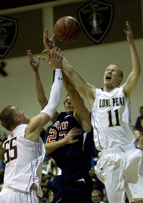 Kim Raff  |  The Salt Lake Tribune (left) Lone Peak players Eric Mika and TJ Haws battles with Brighton player Brandon Miller for a rebound during a game at Lone Peak High School in Highland on November 28, 2012. Lone Peak went on to win the game.