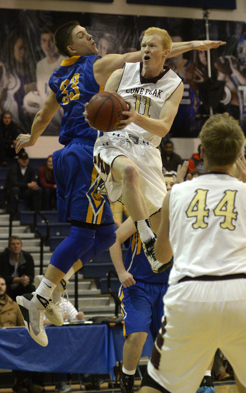 Rick Egan  | The Salt Lake Tribune   TJ Haws goes in for two points for Lone Peak, as Dalton Nixon defends for the Tigers, in prep basketball action in the Great Western Shootout Showcase final game, Orem vs. Lone Peak, at Orem High School, Saturday, December 7, 2013.
