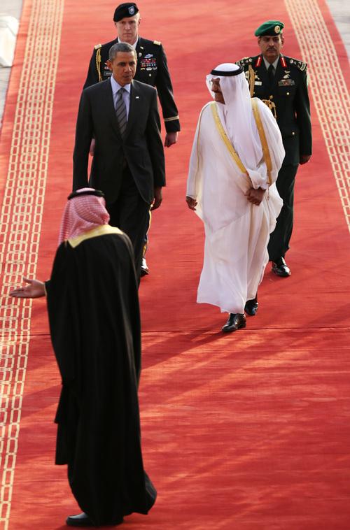 U.S. President Barack Obama, center left, is welcomed by Governor of Riyadh Prince Khalid Bandar bin Abdul-Aziz Al-Saud, center right,  on arriving in Riyadh, Saudi Arabia, on Friday, March 28, 2014. (AP Photo/Hasan Jamali)