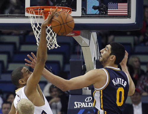 New Orleans Pelicans center Alexis Ajinca (42) battles Utah Jazz center Enes Kanter (0) for a rebound in the first half of an NBA basketball game in New Orleans, Friday, March 28, 2014. (AP Photo/Bill Haber)