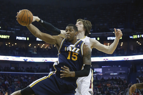 Utah Jazz center Derrick Favors (15) grabs a rebound in front of New Orleans Pelicans forward Luke Babbitt (8) in the first half of an NBA basketball game in New Orleans, Friday, March 28, 2014. (AP Photo/Bill Haber)