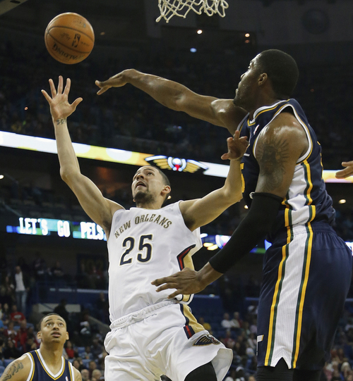 New Orleans Pelicans guard Austin Rivers (25) shoots around Utah Jazz center Derrick Favors (15) in the first half of an NBA basketball game in New Orleans, Friday, March 28, 2014. (AP Photo/Bill Haber)