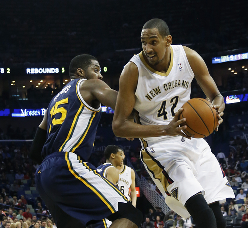 New Orleans Pelicans center Alexis Ajinca (42) gets by Utah Jazz center Derrick Favors (15) in the first half of an NBA basketball game in New Orleans, Friday, March 28, 2014. (AP Photo/Bill Haber)
