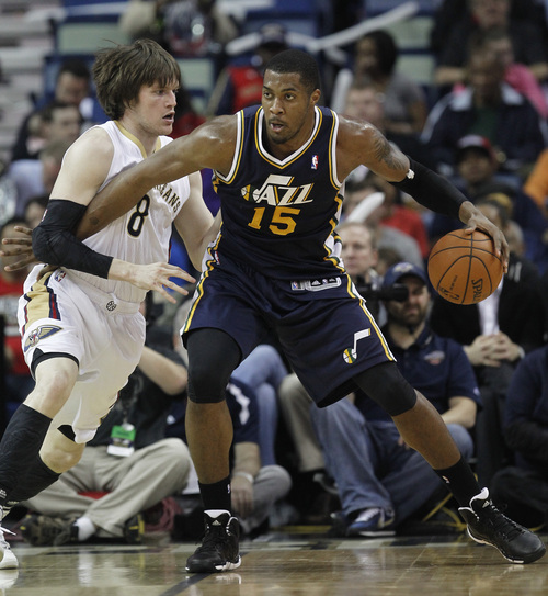 Utah Jazz center Derrick Favors (15) backs into New Orleans Pelicans forward Luke Babbitt (8) in the first half of an NBA basketball game in New Orleans, Friday, March 28, 2014. (AP Photo/Bill Haber)