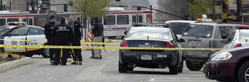 Al Hartmann     The Salt Lake Tribune Salt Police investigate the scene at 300 South and West Temple at 7:30 a.m. Friday morning March 28 where there was an officer involved shooting. Two officers were wounded and the suspect was killed.  Suspects body lies beneath the SUV at right.
