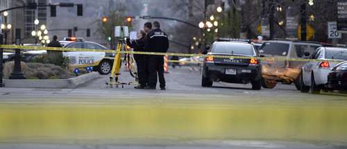 Al Hartmann     The Salt Lake Tribune Salt Lake City Police investigate the scene at 300 South and West Temple at 7:30 a.m. Friday morning March 28 where there was an officer involved shooting. Two officers were wounded and the suspect was killed.