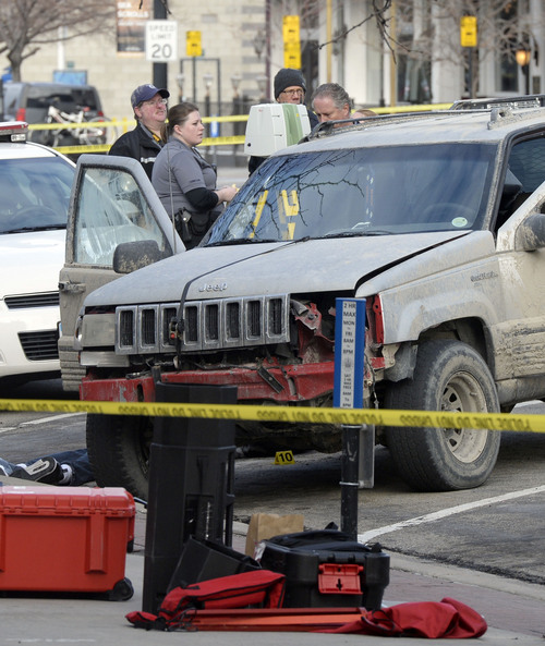 Al Hartmann     The Salt Lake Tribune Salt Lake Police investigate the scene at 300 South and West Temple Friday morning March 28 where there was an officer involved shooting. Two officers were wounded and the suspect was killed.  Suspect was driving the SUV.