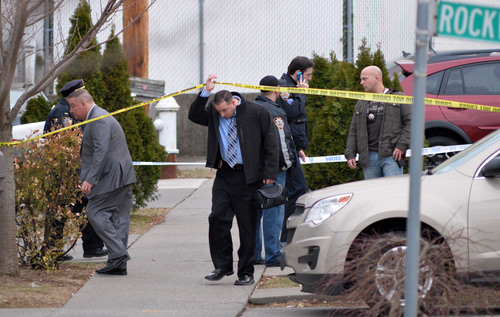 A detective passes under crime scene tape as New York City Police investigate the scene of a double shooting in the Rosebank section of the Staten Island borough of New York, Friday, March 28, 2014. Police say that an elderly man shot his grandson in the head before killing the man's girlfriend, then drove away to take his own life. Police still have no motive of the murder-suicide. (AP Photo/Staten Island Advance, Bill Lyons) NO SALES