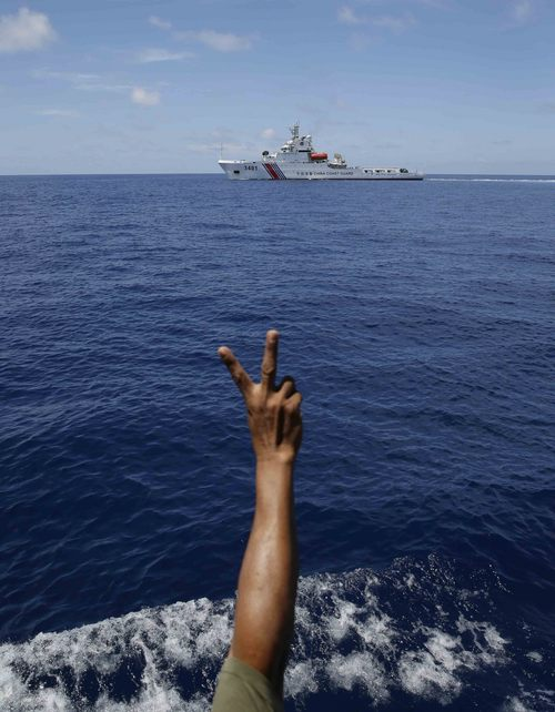 A Philippine Marine gestures at a Chinese Coast Guard vessel which tries to block a Philippine Government vessel AM700 from approaching the Second Thomas Shoal, locally known as Ayungin Shoal,  to resupply and replace fellow marines who were deployed for almost five months Saturday, March 29, 2014 off South China Sea on the West Philippine Sea. (AP Photo/Bullit Marquez)