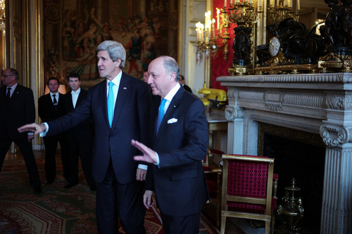 U.S. Secretary of State John Kerry, left, and his French counterpart Laurent Fabius, center, gesture prior to a meeting at the Quai d'Orsay, in Paris, Sunday, March 30, 2014. After a week of travel in the Mideast, Kerry changed course and arrived in Paris Saturday for talks with his Russian counterpart on the Ukraine crisis. (AP Photo/Thibault Camus)
