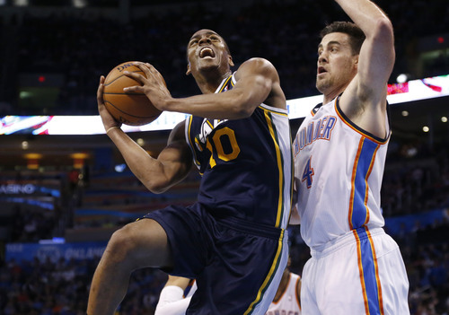 Sue Ogrocki | The Associated Press Utah Jazz guard Alec Burks (10) goes up for a shot in front of Oklahoma City Thunder forward Nick Collison (4) in the fourth quarter of an NBA basketball game in Oklahoma City, Sunday, March 30, 2014. Oklahoma City won 116-96. (AP Photo/Sue Ogrocki)