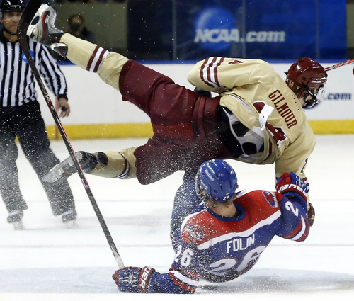 Boston College's Adam Gilmour (14) and  UMass Lowell's Christian Folin (26) crash going for the puck in the first period of the NCAA Northeast Regional hockey final in Worcester, Mass., Sunday, March 30, 2014. (AP Photo/Elise Amendola)