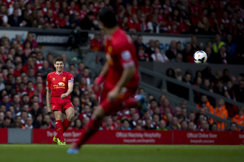 Liverpool's Steven Gerrard fires a pass across the pitch during his team's 4-0 win against Tottenham in their English Premier League soccer match at Anfield Stadium, Liverpool, England, Sunday March 30, 2014. (AP Photo/Jon Super)
