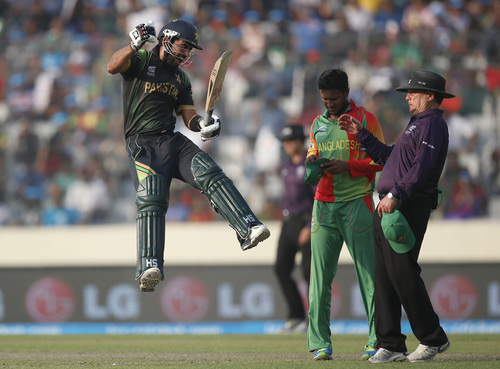 Pakistan batsman Ahmed Shehzad, left, leaps in the air to celebrate scoring a century during their ICC Twenty20 Cricket World Cup match against Bangladesh in Dhaka, Bangladesh, Sunday, March 30, 2014. (AP Photo/Aijaz Rahi)