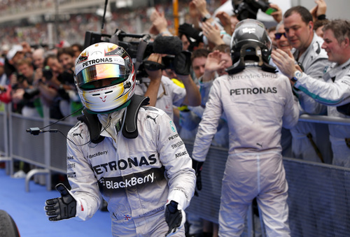 Mercedes driver Lewis Hamilton, left, of Britain celebrates after winning the Malaysian Formula One Grand Prix as teammate Mercedes driver Nico Rosberg of Germany is congratulated by their team at Sepang International Circuit in Sepang, Malaysia, Sunday, March 30, 2014. (AP Photo/Vincent Thian)